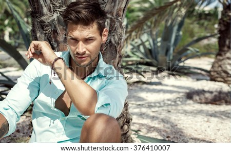 Portrait of handsome man under the palm tree - stock photo