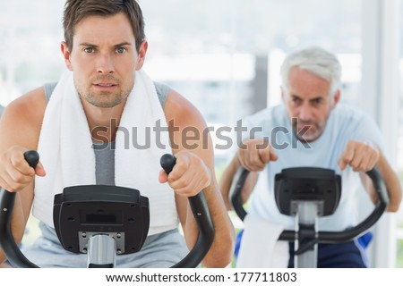 Portrait of handsome man using exercise bike at gym - stock photo
