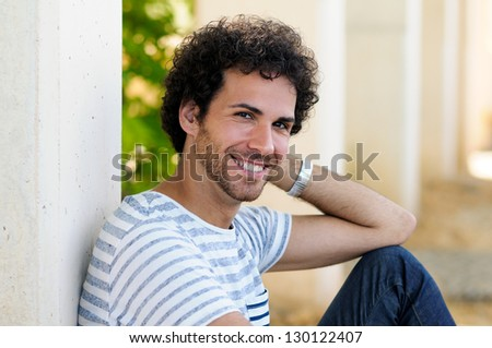 Portrait of handsome man with curly hairstyle smiling in urban background - stock photo