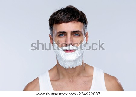 Portrait of handsome man with foam on face - stock photo