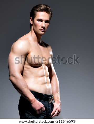 Portrait of handsome man with sexy muscular beautiful body posing at studio. - stock photo