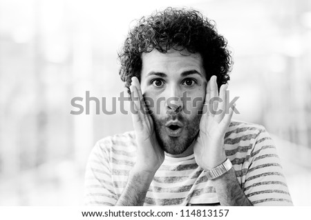 Portrait of handsome man with surprise face in urban background - stock photo