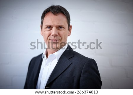 Portrait of handsome mature businessman looking at camera against grey background  - stock photo