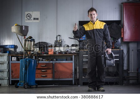 Portrait of handsome mechanic based on car in auto repair shop smiling  - stock photo