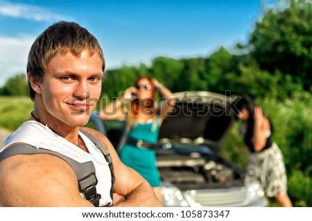 Portrait of handsome mechanic with two helpless women and broken car on background - stock photo