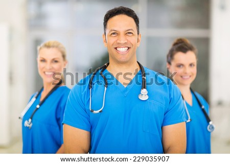 portrait of handsome medical doctor with colleagues on background - stock photo