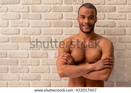 Portrait of handsome naked Afro American man looking at camera and smiling, standing with crossed arms against white brick wall - stock photo