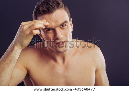 Portrait of handsome naked man examining wrinkles on his face, on a dark background - stock photo