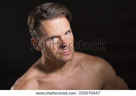 Portrait of handsome rugged Caucasian male athlete with muscular fit shirtless body on black background - stock photo