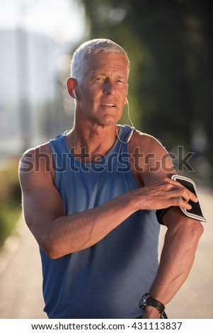 portrait of handsome senior jogging man while relaxing  and take break after morning run - stock photo