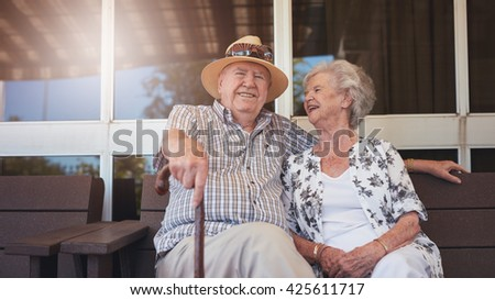 Portrait of handsome senior man sitting with his wife on a bench outside their house. Retired couple taking a break and relaxing outside their home. - stock photo
