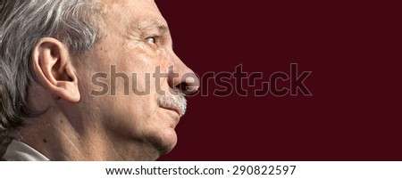 Portrait of handsome senior man with a tired expression on dark red background with copy-space - stock photo