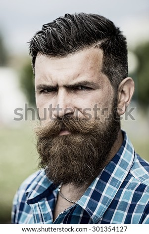 Portrait of handsome serious unshaven guy with long beard and hendlebar moustache in checkered white and light blue shirt looking forward standing outdoor, vertical picture - stock photo