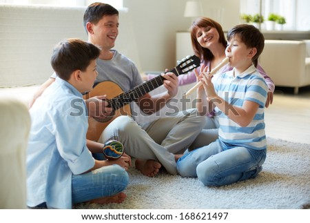 Portrait of handsome siblings and their father playing musical instruments at home - stock photo
