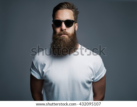 Portrait of handsome single bearded young Caucasian man wearing sunglasses with serious expression and white short sleeve shirt over gray background - stock photo