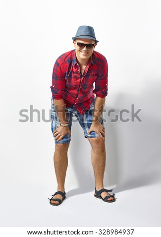 Portrait of handsome smiling man in hat and sunglasses - stock photo