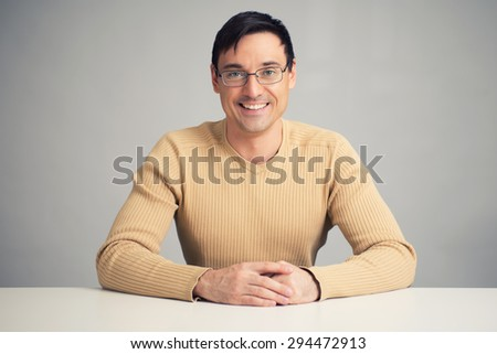 portrait of handsome smiling man on a desk - stock photo