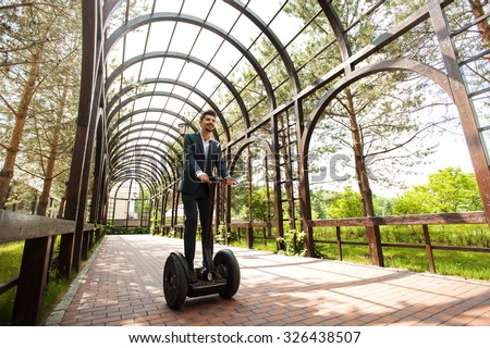 Portrait of handsome smiling young businessman wearing suit. Man using segway. Wooden greenhouse as background - stock photo