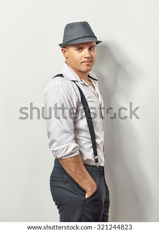 Portrait of handsome smiling young man in hat and suspenders - stock photo