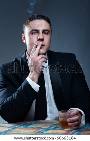 Portrait of handsome smoking young man with glass of whiskey - stock photo