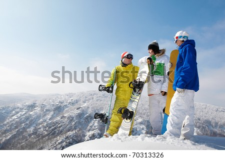 Portrait of handsome snowboarders standing on the mountain - stock photo