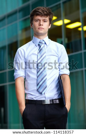 Portrait of handsome standing attractive businessman with briefcase, background - stock photo