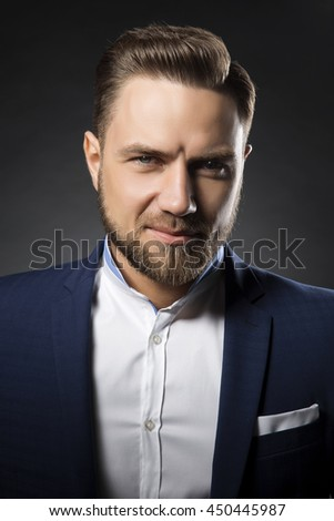 Portrait of handsome stylish caucasian bearded young man in elegant blue suit and white shirt with perfect hair style smiling when looking at camera.  - stock photo