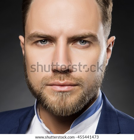 Portrait of handsome stylish caucasian bearded young man in elegant blue suit and white shirt with perfect hair style looking at camera.  - stock photo