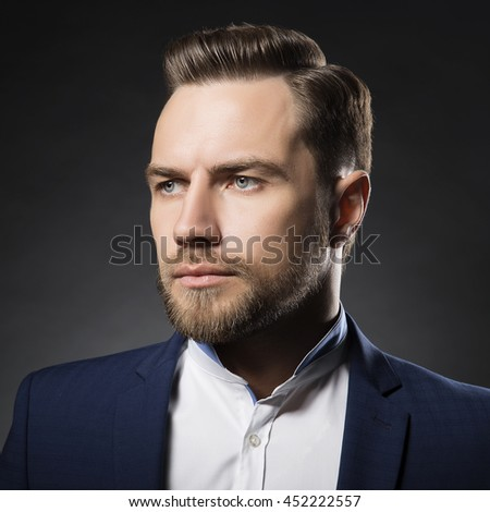 Portrait of handsome stylish caucasian young man in elegant blue suit with perfect hair style.  - stock photo