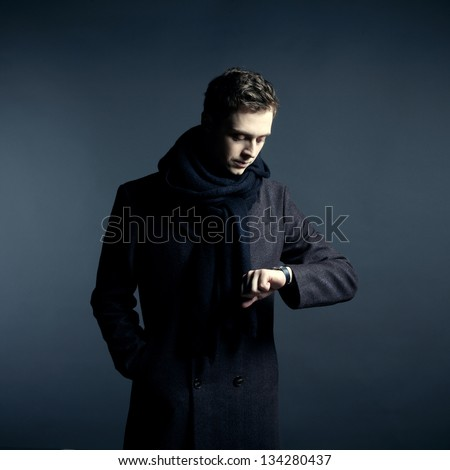 Portrait of handsome stylish man in coat with watch - stock photo
