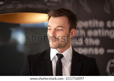 Portrait of handsome stylish man in elegant black suit. Cool businessman standing on dark background in cafe and looking away  - stock photo