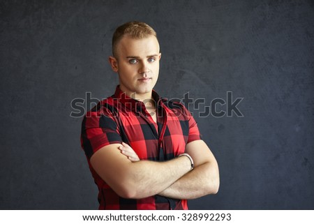 Portrait of handsome stylish man in plaid shirt on grey textured background - stock photo