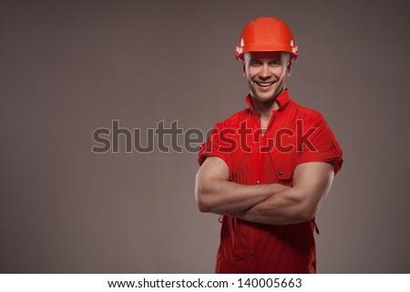 Portrait of handsome worker in helmet isolated on dark background - stock photo