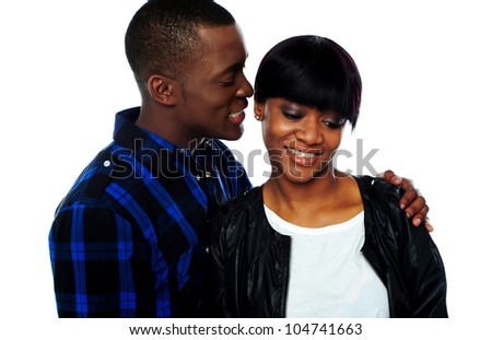 Portrait of handsome young african man whispering in his girlfriends ear - stock photo
