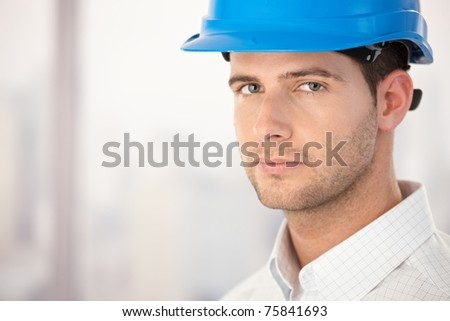 Portrait of handsome young architect wearing helmet.? - stock photo