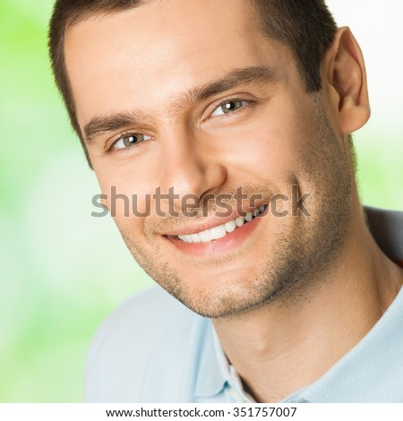 Portrait of handsome young attractive smiling man, outdoor - stock photo