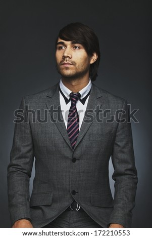 Portrait of handsome young business executive looking away. Mixed race businessman in suit isolated on black background. - stock photo