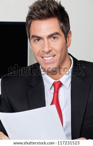 Portrait of handsome young businessman at office - stock photo