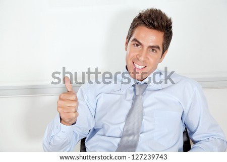 Portrait of handsome young businessman gesturing thumbs up in office - stock photo