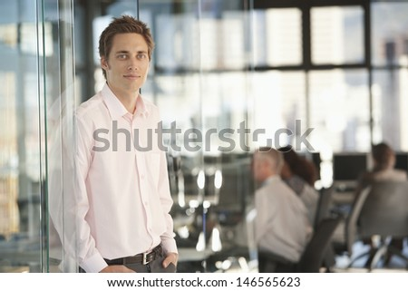 Portrait of handsome young businessman leaning on glass door with colleagues working in background - stock photo