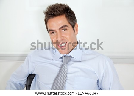 Portrait of handsome young businessman relaxing in office - stock photo