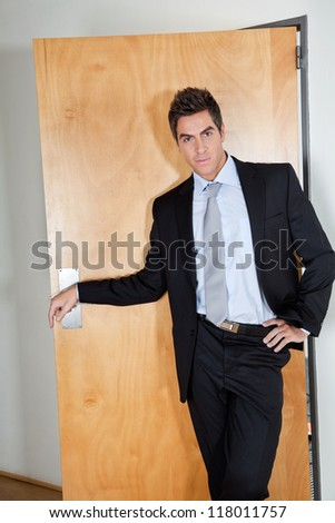 Portrait of handsome young businessman standing with hand on hip in office - stock photo