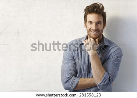 Portrait of handsome young casual man smiling over wall. - stock photo
