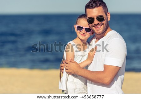 Portrait of handsome young dad and his cute little daughter in sun glasses hugging, looking at camera and smiling, sunny seaside in the background - stock photo
