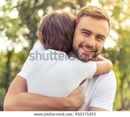 Portrait of handsome young dad looking at camera and smiling while hugging his cute little boy, trees in the background - stock photo