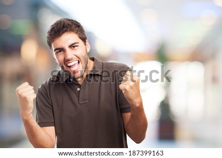 portrait of handsome young european man doing a winner gesture - stock photo