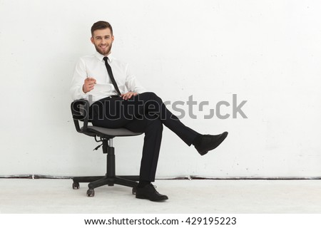 Portrait of handsome young guy sitting in chair against white wall. - stock photo