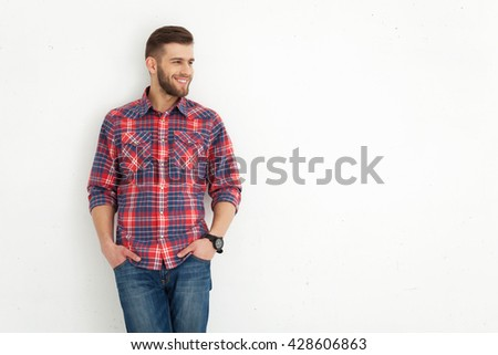 Portrait of handsome young guy standing against white wall. - stock photo
