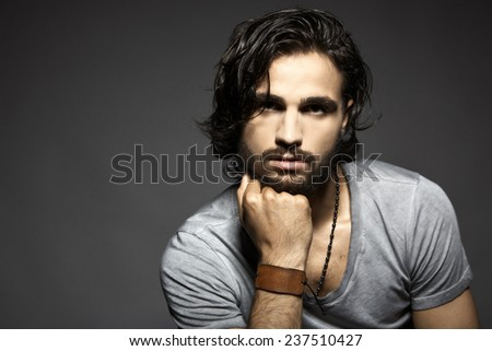 Portrait of handsome young man against grey background - stock photo