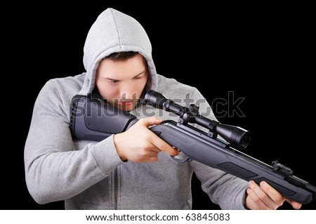 portrait of handsome young man in gray jacket with hood aiming the sniper rifle on black - stock photo